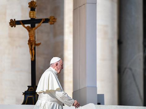 Papst Franziskus geht an einem Kruzifix vorbei