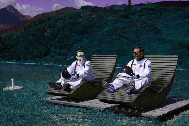 Kurt Razelli und Matthias Strolz in Raumanzügen auf Holzliegestühlen