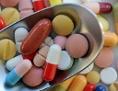 Verschiedene Pillen und Tabletten liegen auf einem Löffel