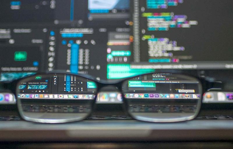 Brille liegt vor einem Computermonitor
