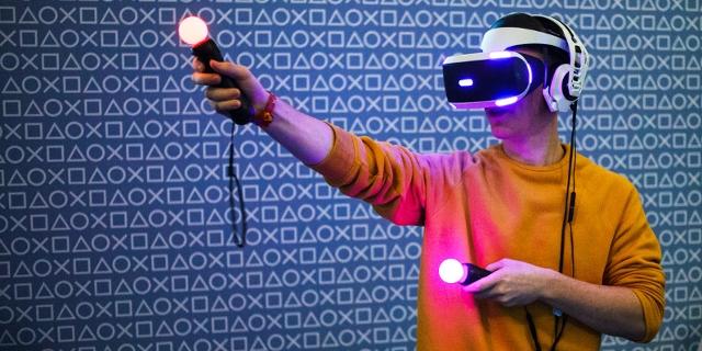 Person mit VR-Brille und leuchtenden Game-Controllern
