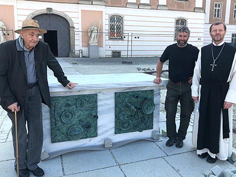 """Daniel Spoerri (li.) mit dem von ihm geschaffenen """"Reich-Arm-Altar"""", Wilhelm Scherübl und Abt Reinhold Dessl"""