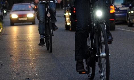 Ein Fahradfahrer ohne Licht fährt hinter einem Fahrradfahrer, der sein Licht eingeschaltet hat