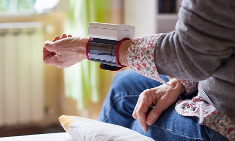 Frau misst sich selbst den Blutdruck