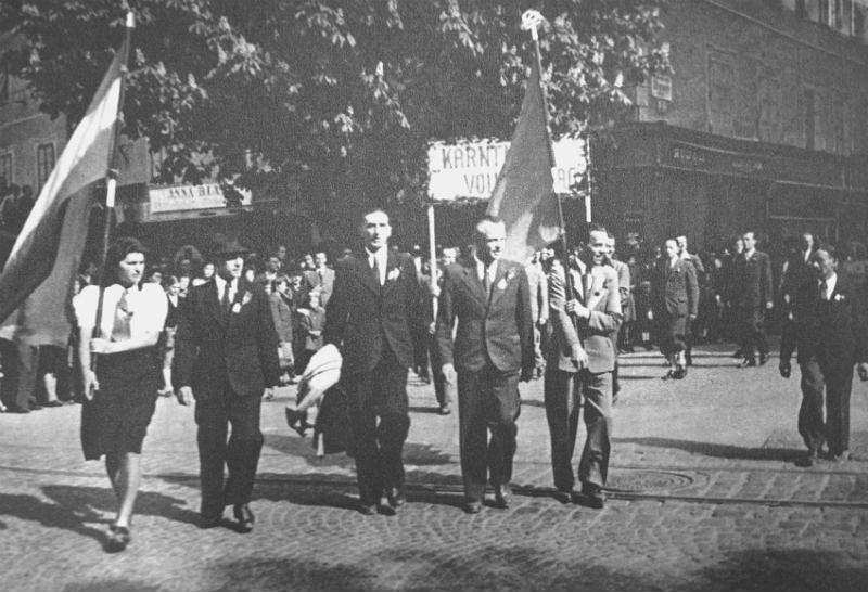 Anzug und Krawatte: Aufmarsch der Kommunisten mit Fahnen