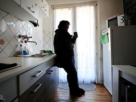 Eine Frau steht in einer Küche im Gegenlicht