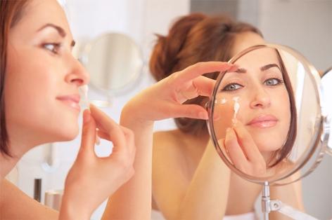 Frau trägt Gesichtscreme auf
