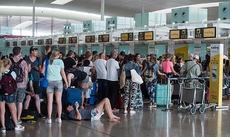 Passagiere warten vor einem Vueling-Abflugschalter