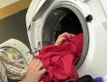 Mann füllt Wäsche in eine Waschmaschine