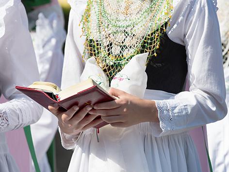 Eine Trau in Tracht hält ein Gebetsbuch