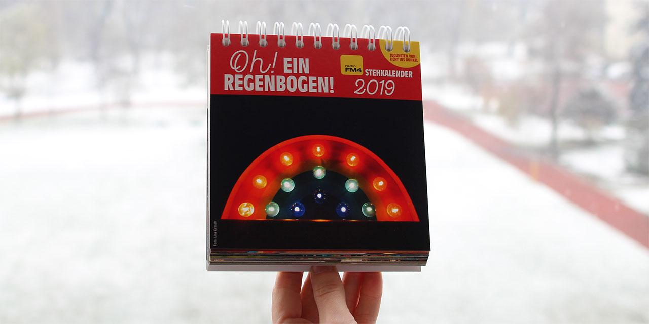 Stehkalender mit Regenbogen vor verschneiter Landschaft