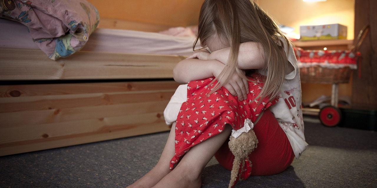 Kind, das seinen Kopf in den Armen vergräbt