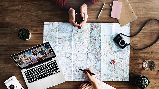 Reiseplanung mit Karte und Laptop
