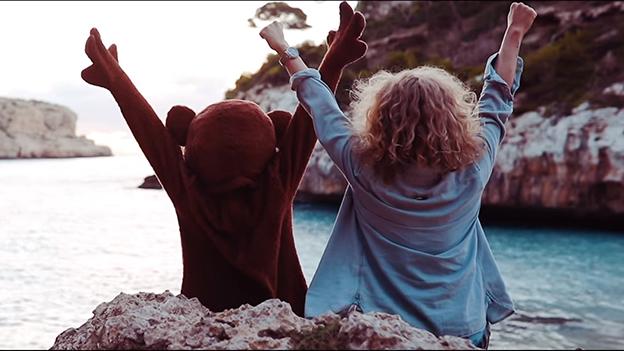 Ein Bär und Thorsteinn Einarsson sitzen am Meer und strecken die Arme in die Luft
