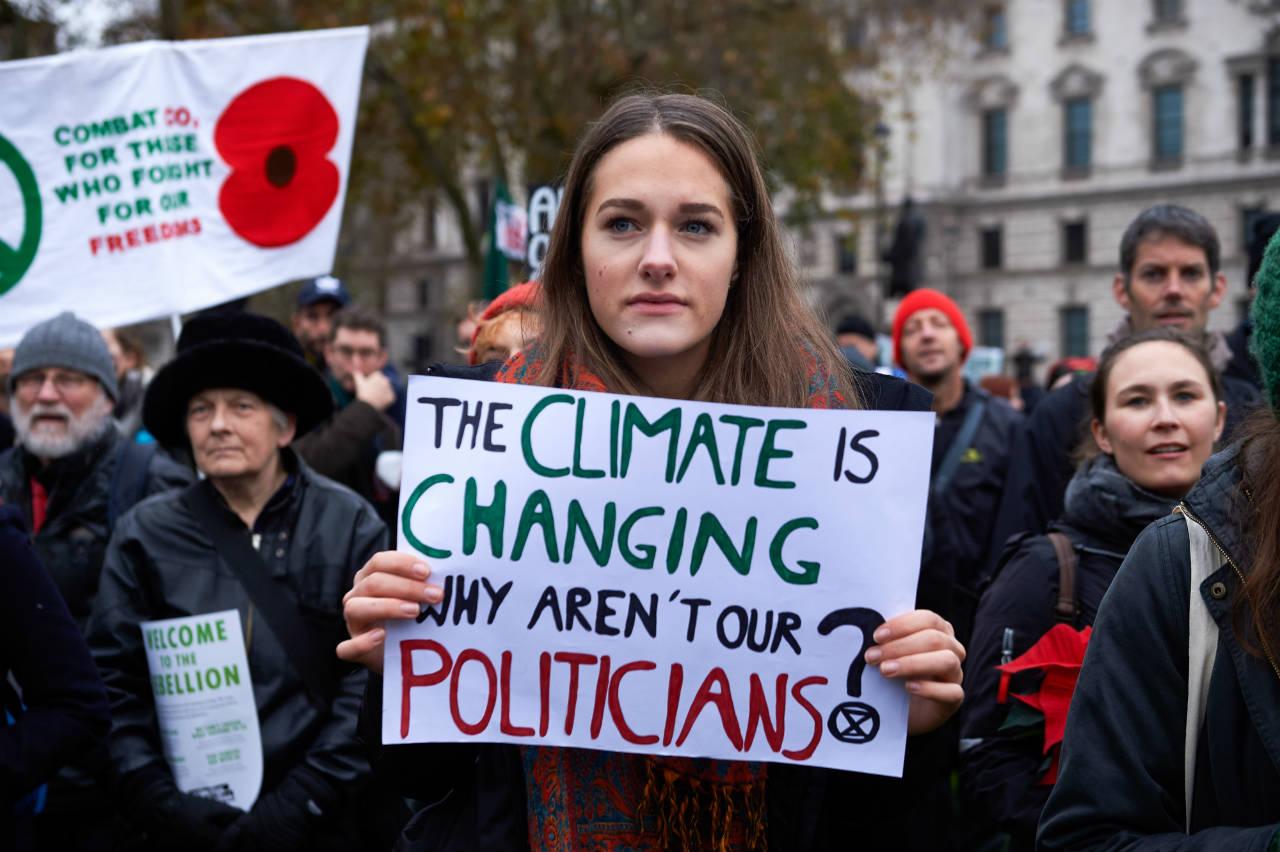 """Demonstrantin hält ein Schild mit der AUfschrift """"The climate is changing, why aren't our politicians?"""""""