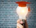 Eine leuchtende Glühbirne mit aufgesetztem akademischen Hut, Universitätsabschluss, Genie, Kult, Intelligenz, Heureka, Idee