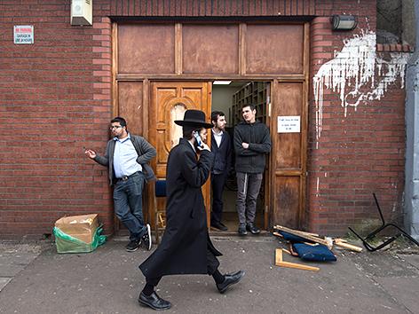 Strengreligiöser jüdischer Mann geht telefonierend an der Synagoge der Londoner Gemeinde in Stamford Hill vorbei