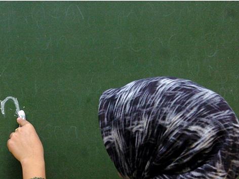 Eine Frau mit Kopftuch von hinten vor einer Tafel