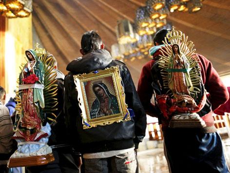 Drei Männer mit auf den Rücken gebundenen Bildern und Statuen der Jungfrau von Guadalupe