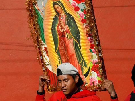 Ein Mann trägt ein Bild der Jungfrau von Guadalupe auf den Schultern