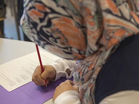 Muslimisches Mädchen in der Volksschule mit Kopftuch schreibt