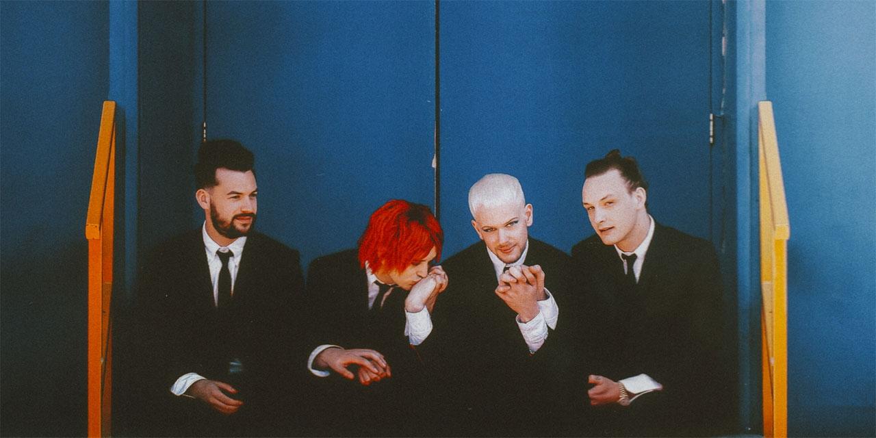 Die vier Bandmitglieder sitzend und händehaltend auf einem Treppenaufgang