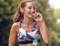 Eine Sportlerin isst einen Proteinriegel