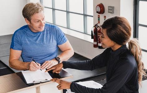 Mann schreibt sich in einem Fitnesscenter ein