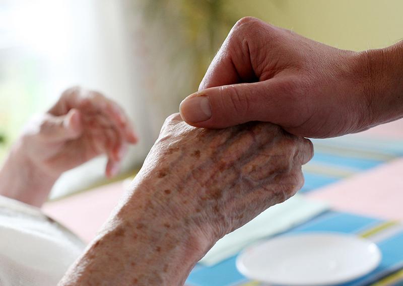 Eine Pflegerin hält die Hand einer alten Frau.
