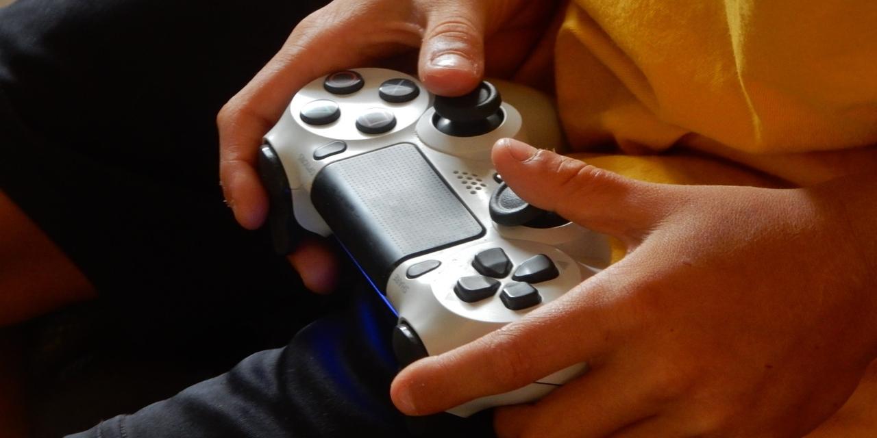 Eine Person spielt an einem Gamecontroller.