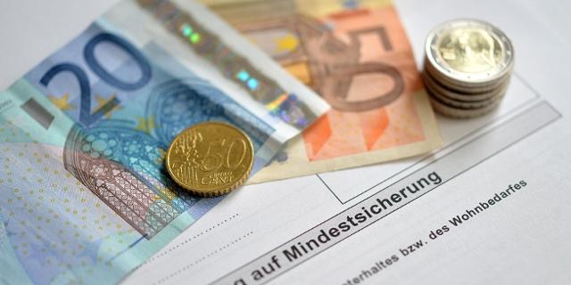 Geldscheine und Münzen auf einem Antrag zur Mindestsicherung