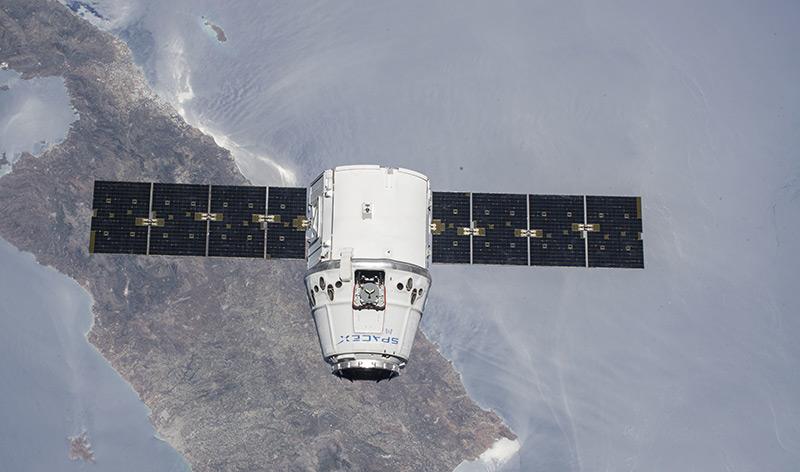 Luftbild: Raumfrachter Dragon über der Erde
