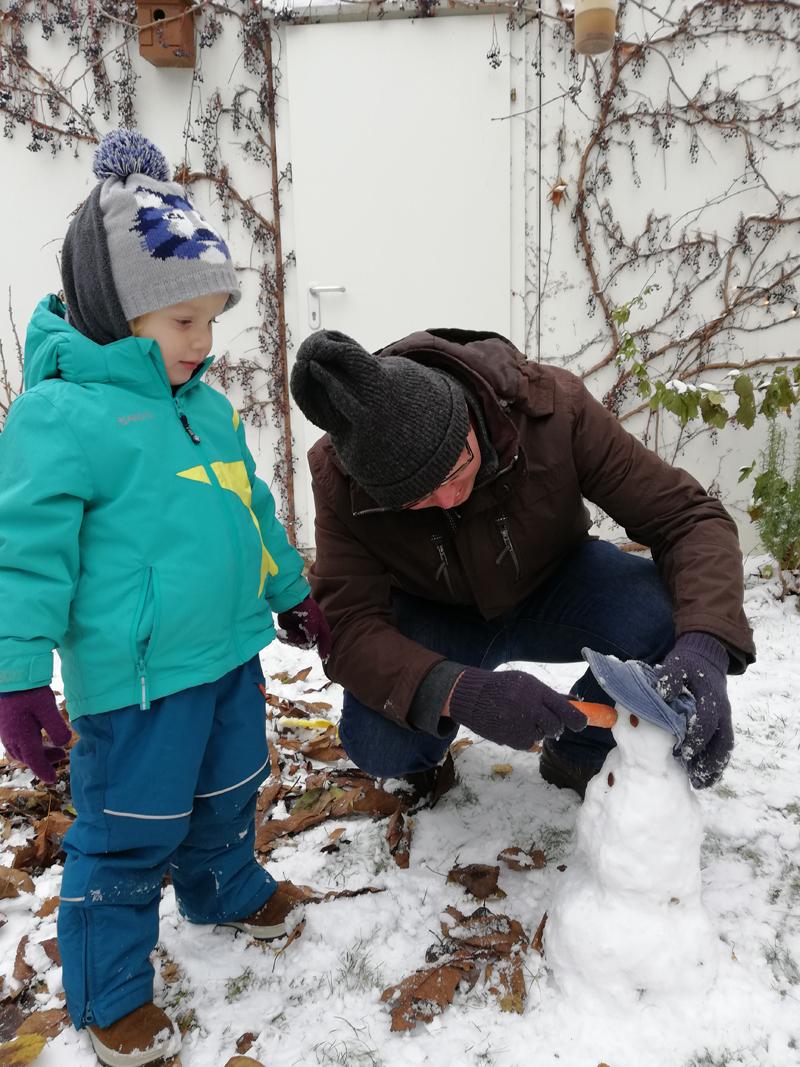 Gregor Johannssón und sein Sohn beim Schneemann bauen
