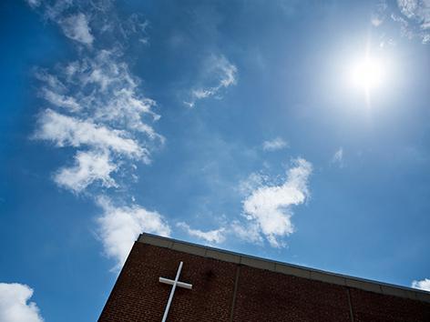 Ein Gebäude mit einem Kreuz vor einem großen Stück Himmel