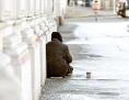 Ein Obdachloser sitzt auf einer winterlichen Straße