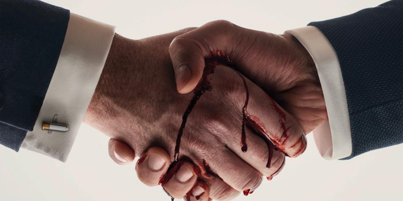 Zwei Hände schütteln sich, sie triefen vor Blut
