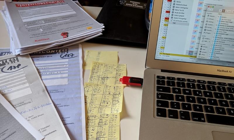 Anmeldeformulare, Post-its mit Notizen und ein Laptop, von dem aus die Musik gespielt wird.