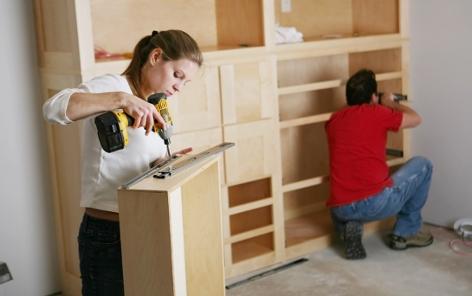 Eine Frau und ein Mann bauen ein Regal zusammen