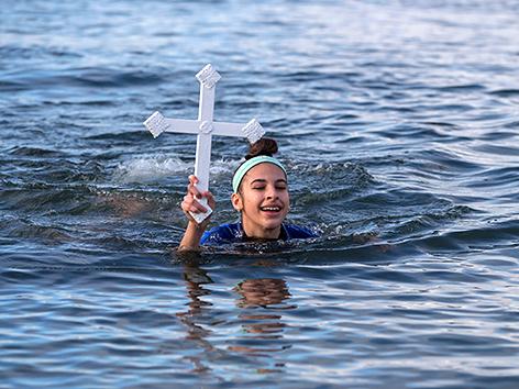 Ein Mädchen schwimmt mit Kreuz in der Hand im Eiswasser zum griechisch-orthodoxen Epiphaniasfest, Vancouver, British Columbia