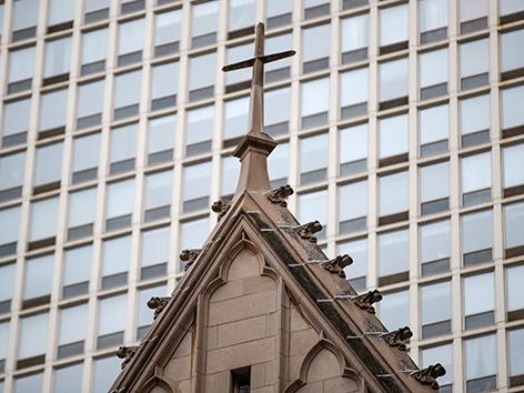 Ein Kirchendach vor einem Wolkenkratzer