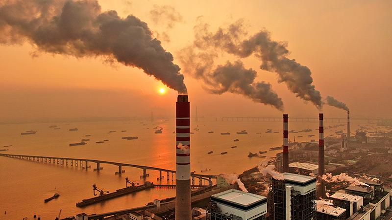 Schlote eines Kohlekraftwerks an der Küste