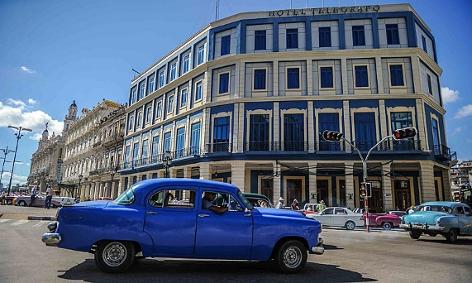 Ein Oldtimer vor einem Hotel in Havanna