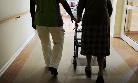 Ein Altenpfleger begleitet eine Frau mit Rollator