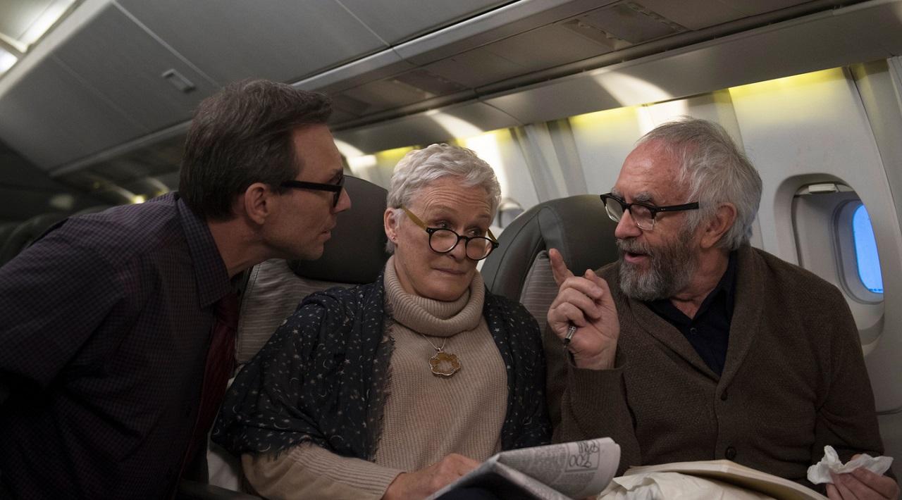 Glenn Close und Jonathan Pryce als Joan und Joe Castleman im Flugzeug. Im Gespräch mit einem Journalisten.
