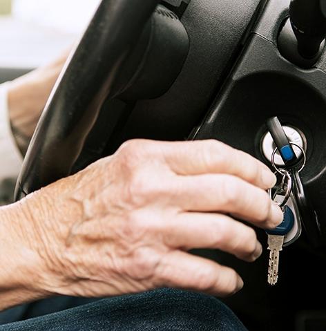 Hände am Zündschloss eines Autos