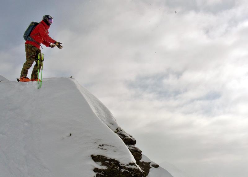 Roman Rohrmoser wirft Schnee von einer Klippe
