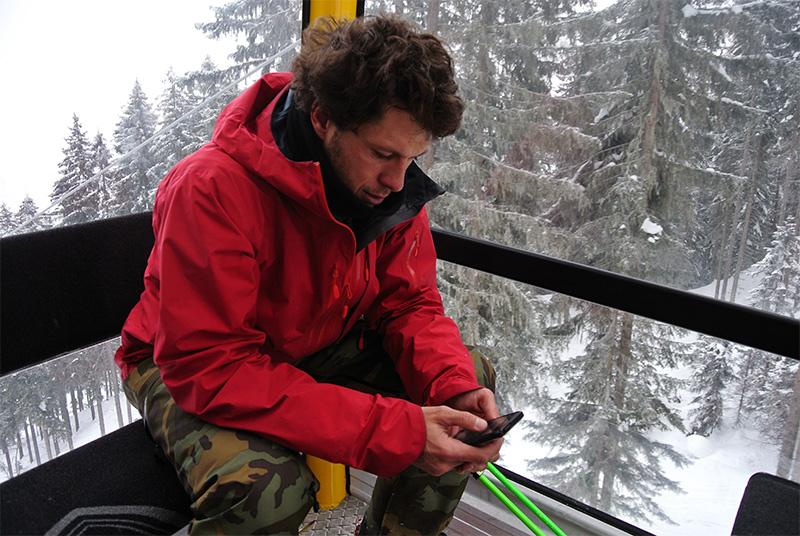 Roman Rohrmoser in der Schigondel mit Smartphone in der Hand