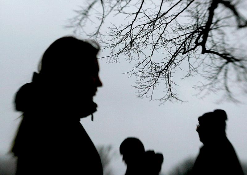 Die Silhouette einer Frau vor einem dunklen Baum.