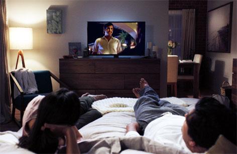 Ein Mann und eine Frau schauen im Bett liegend auf einen Fernseher