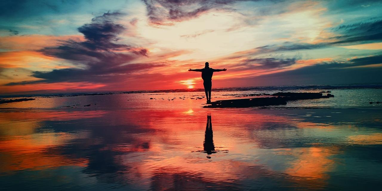 einzelne Person glücklich vor argem Sonnenuntergang